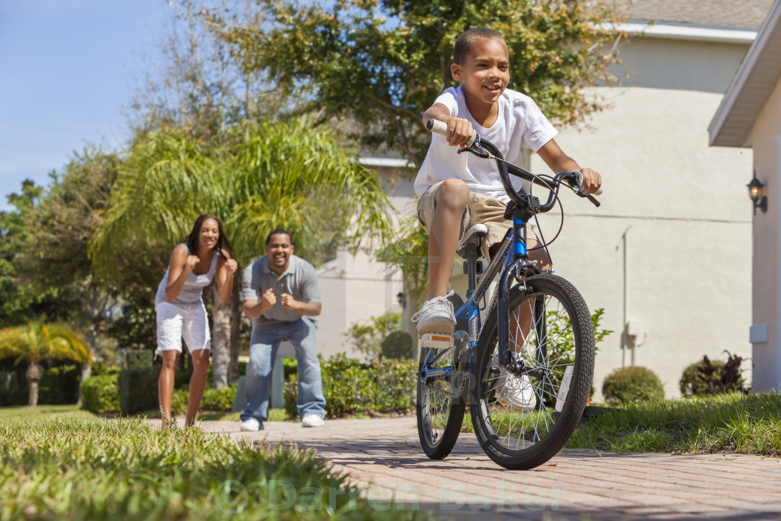 """African American Family WIth Boy Riding Bike & Happy Parents"" stock image"