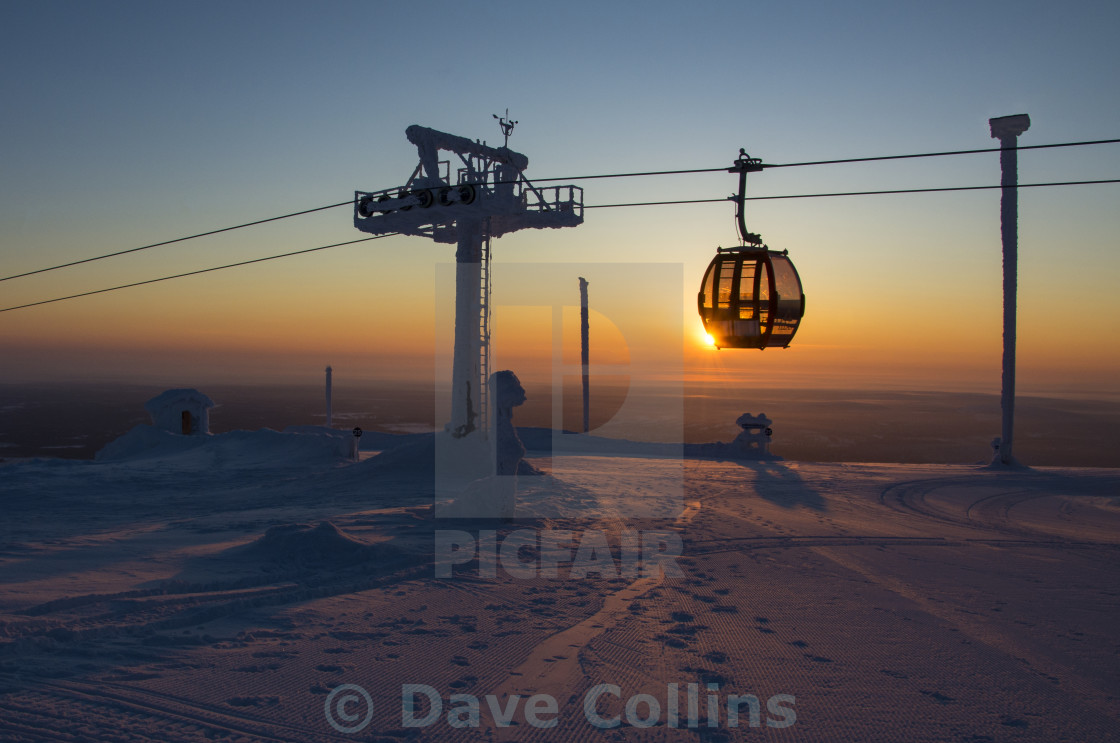 """""""Cable Car passes the setting sun. Yllas, Finland"""" stock image"""
