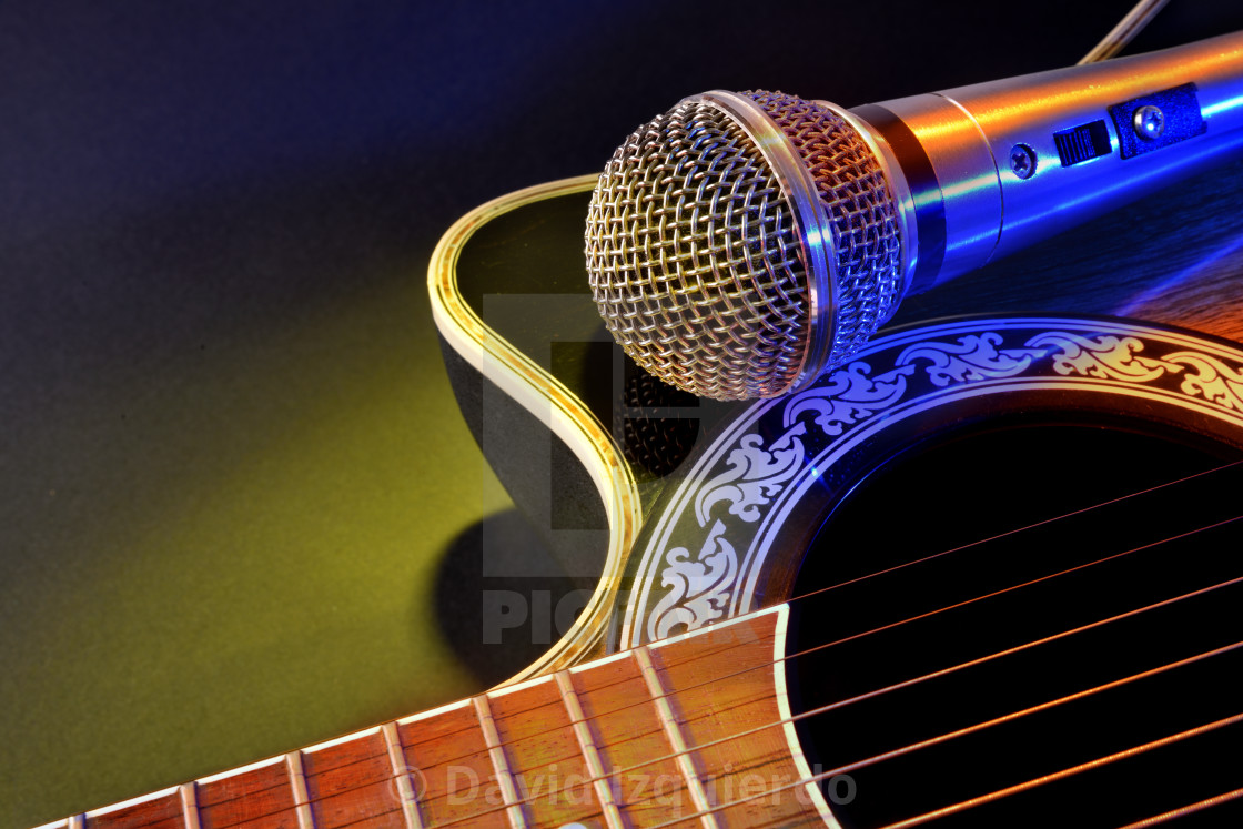 Acoustic guitar and microphone isolated with yellow and blue lights