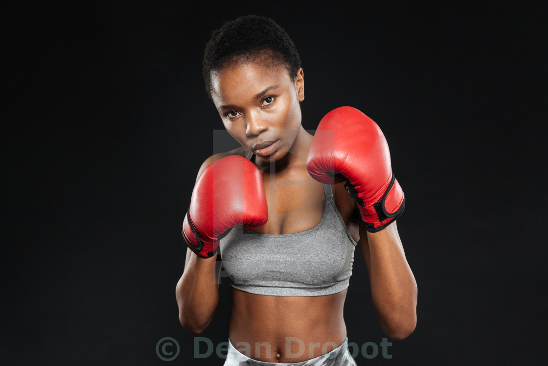 """""""Fitness girl in boxing gloves fighting on black background"""" stock image"""