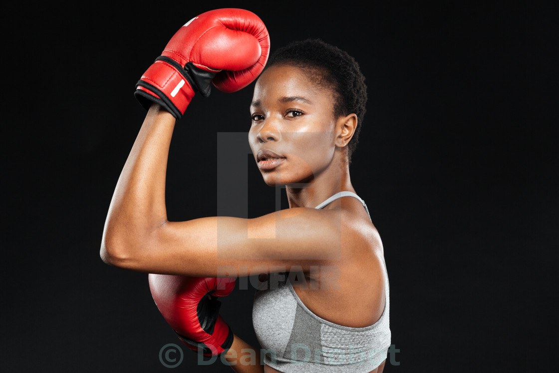 """Sporty woman in boxing gloves over gray background"" stock image"