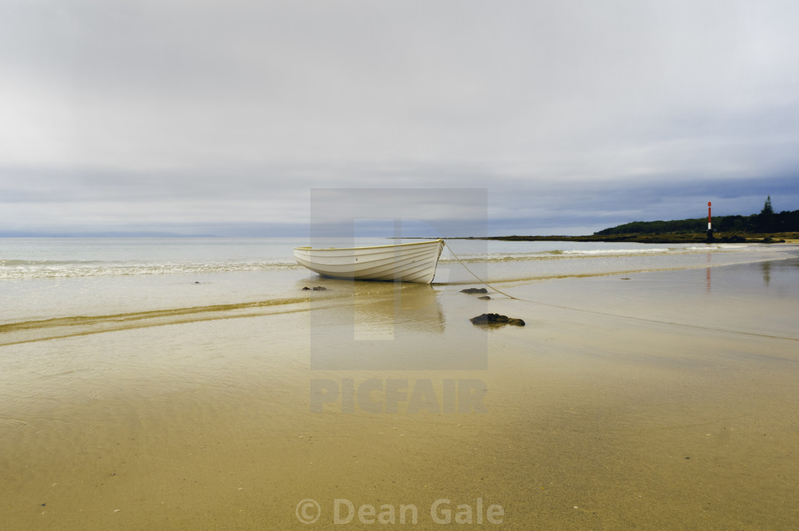 """Currarong on the NSW South Coast of Australia. There's a storm coming in. A beautiful wooden boats sits in the ebbing tide"" stock image"