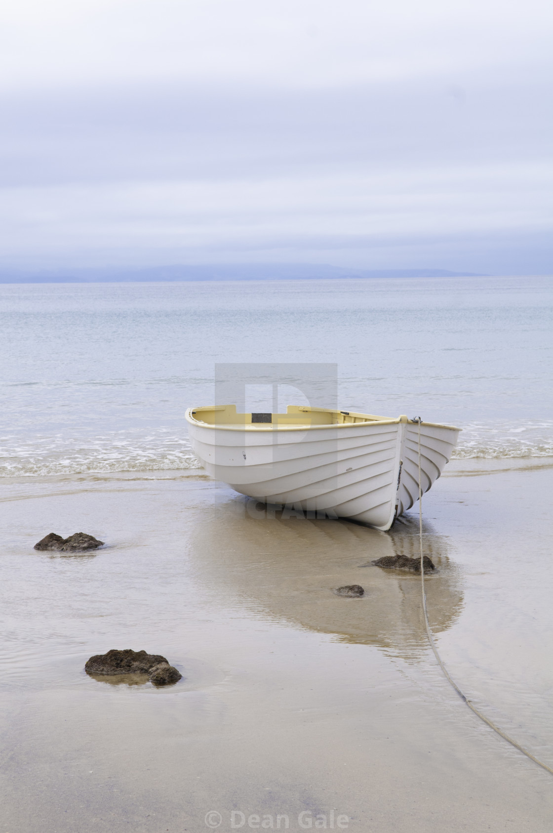 """A wooden boat sits at anchor in the ebbing tide"" stock image"