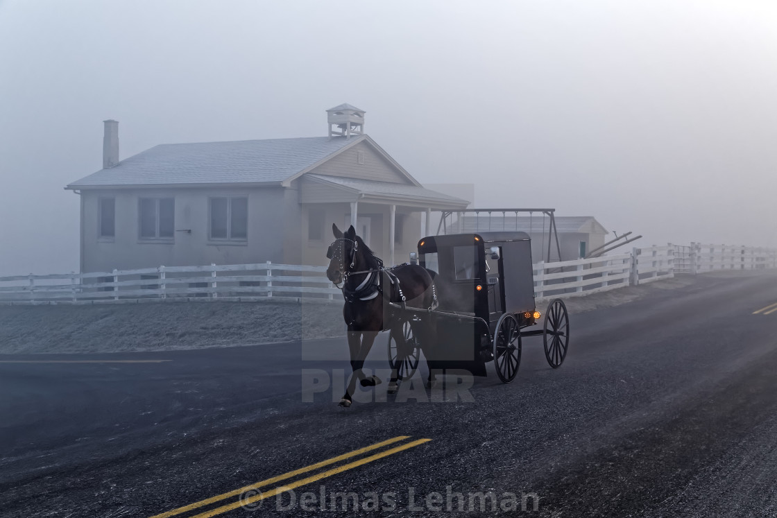 """A Horse and Carriage Passes an Amish School House"" stock image"