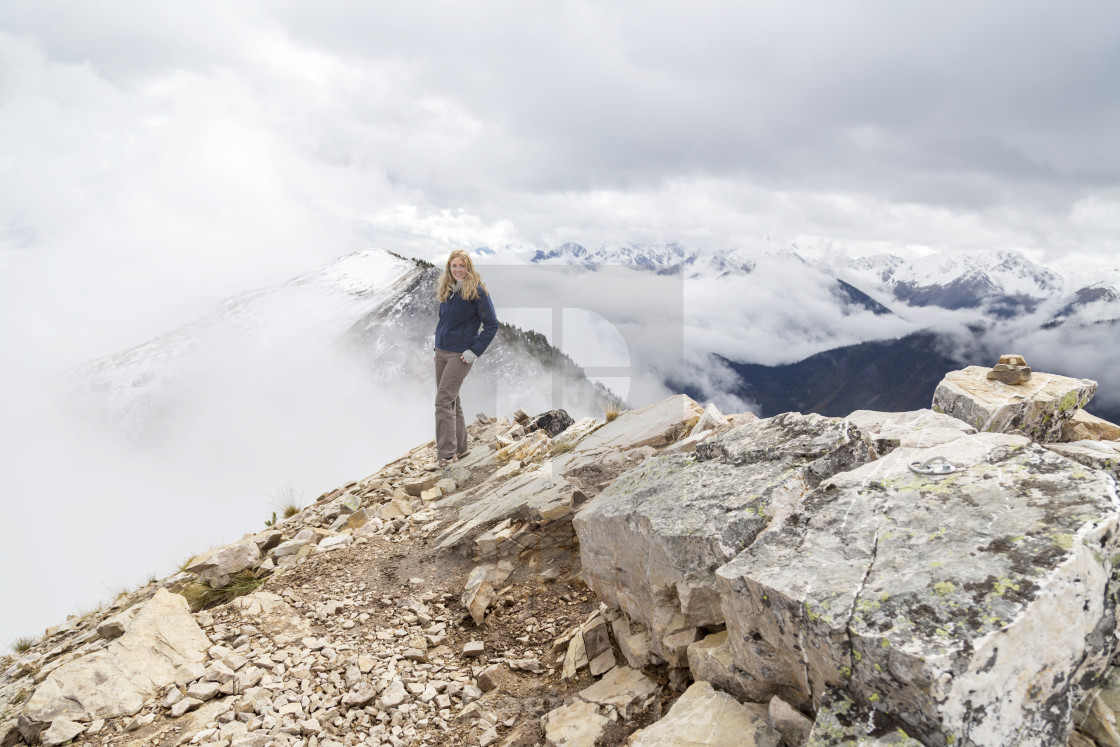 """A female hiker reaches the mountain summit and poses for a photo of the..."" stock image"