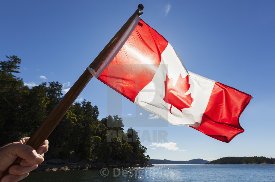 A Man Holds A Canadian Flag Into The Sun With The Gulf