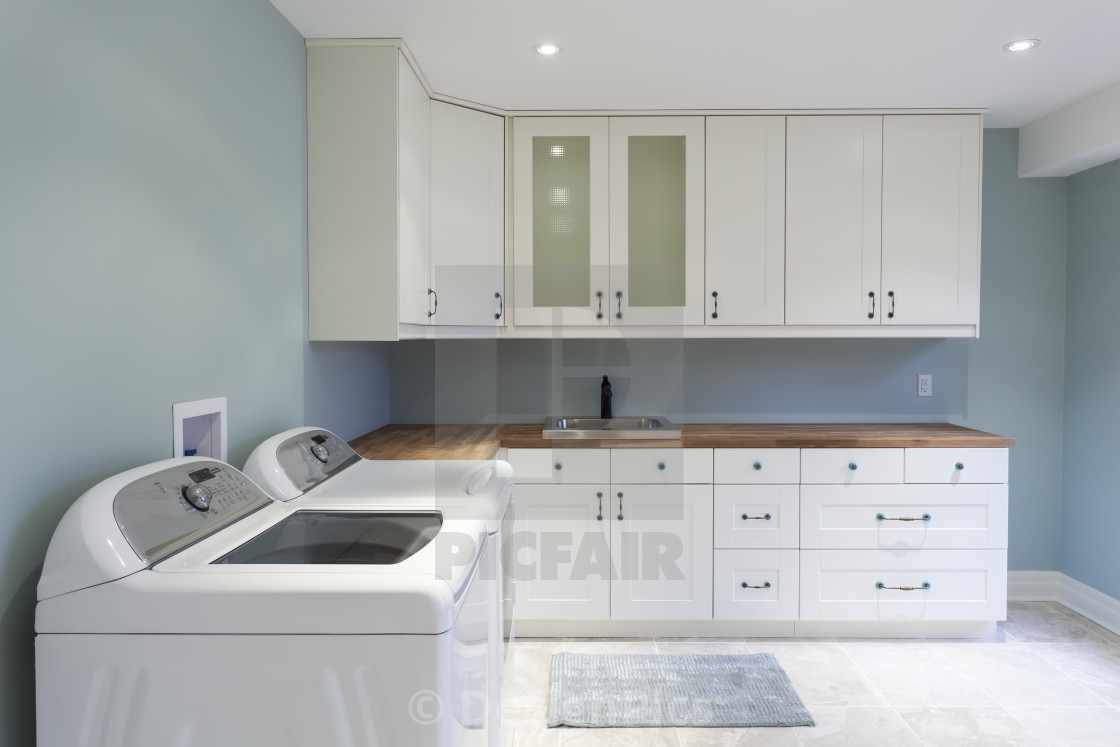 A New Residential Laundry Room With White Cabinets And Blue