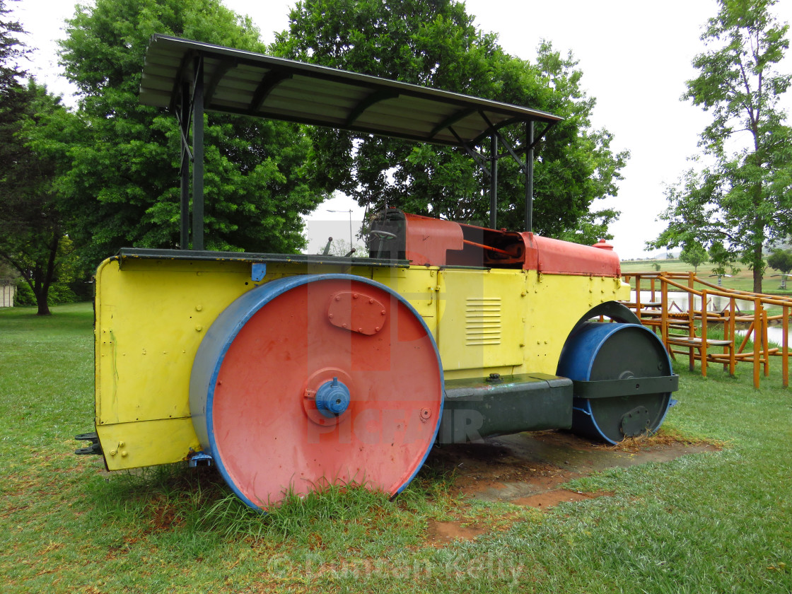 """""""An old steamroller becomes a childs plaything."""" stock image"""
