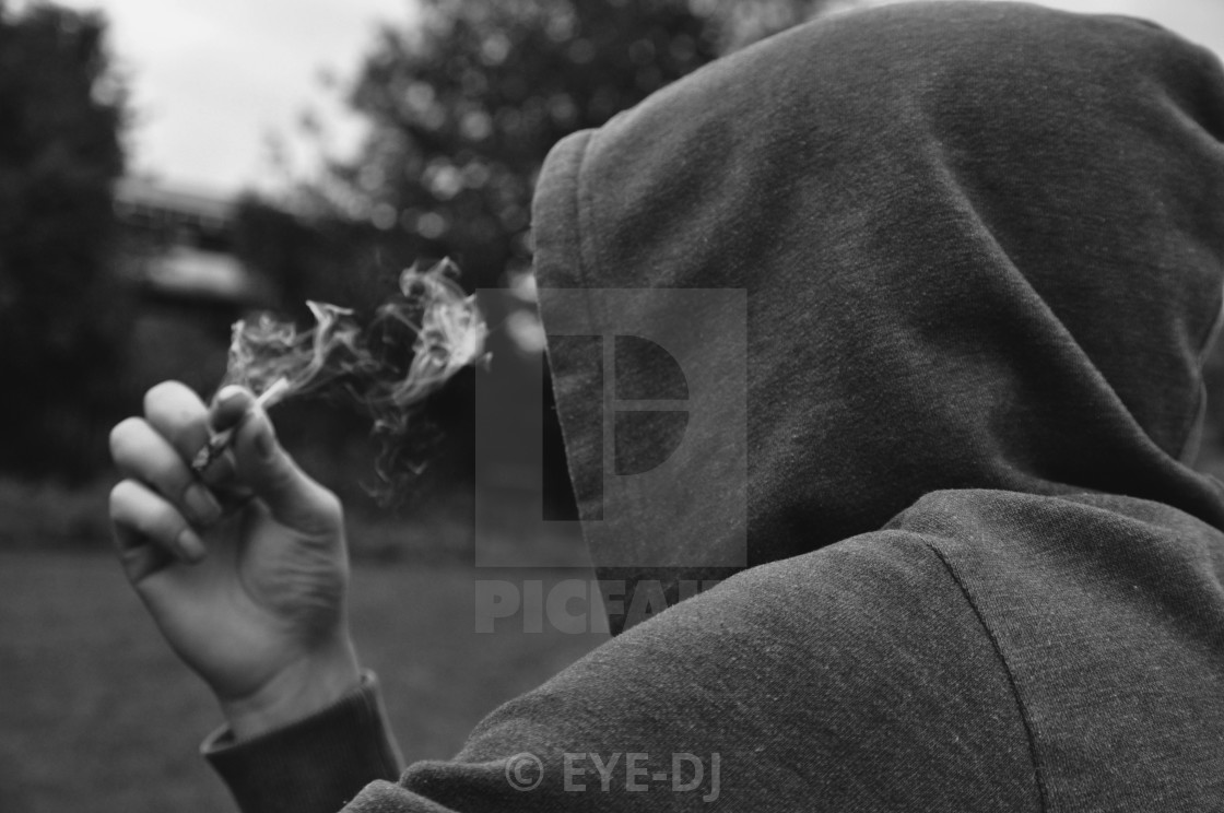 """Mysterious faceless person smoking wearing a hood"" stock image"