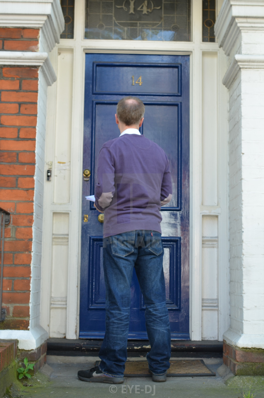 """Canvasser knocking on a blue door and waiting outside"" stock image"