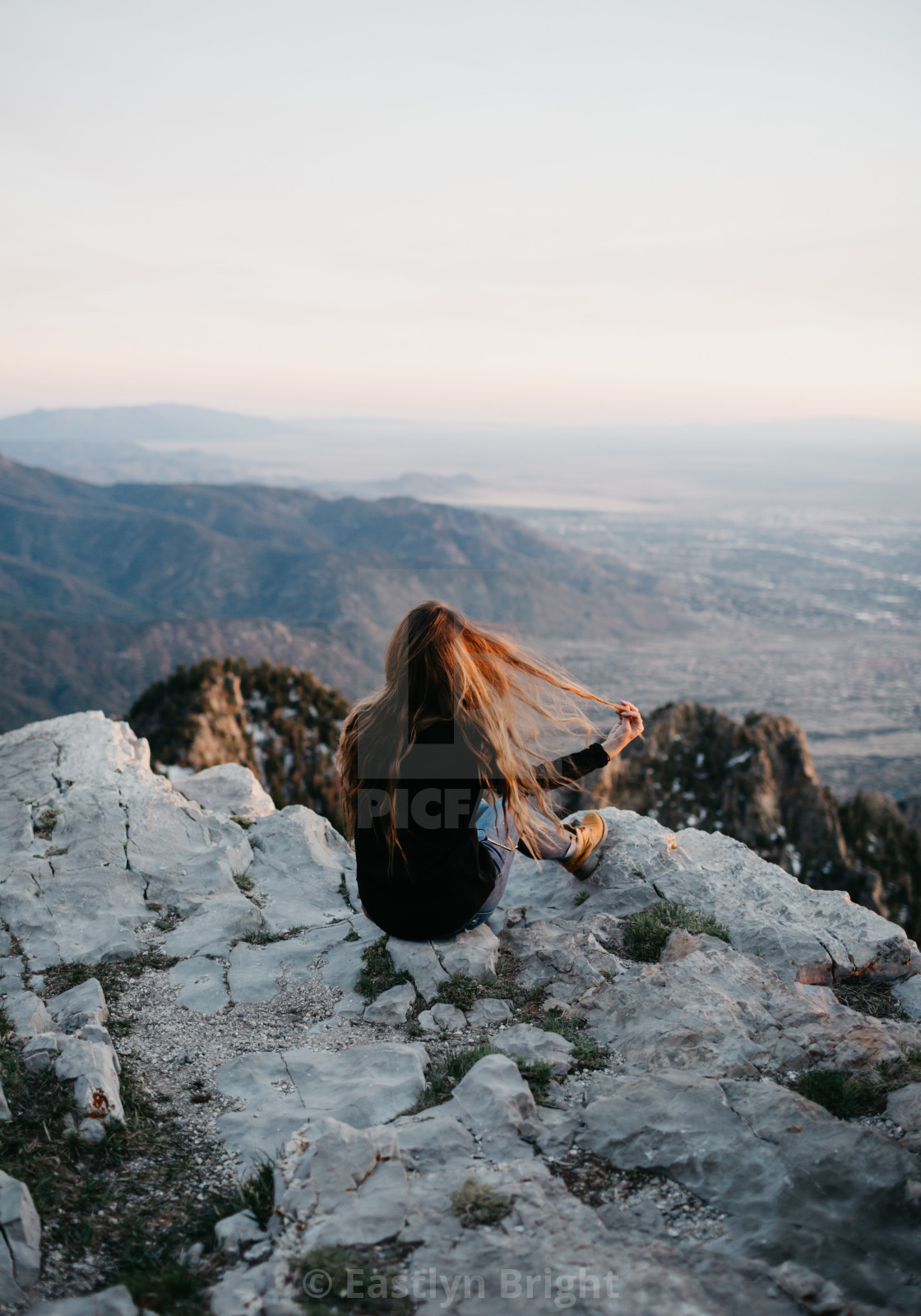 """""""A Woman Sitting on the Top of A Mountain with Hand in Her Hair"""" stock image"""