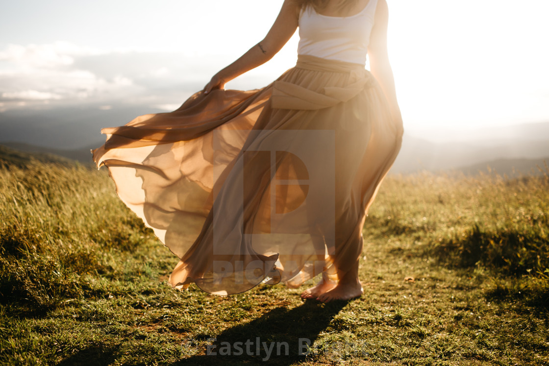 """woman wearing a long skirt blowing in the wind in the summer sun"" stock image"
