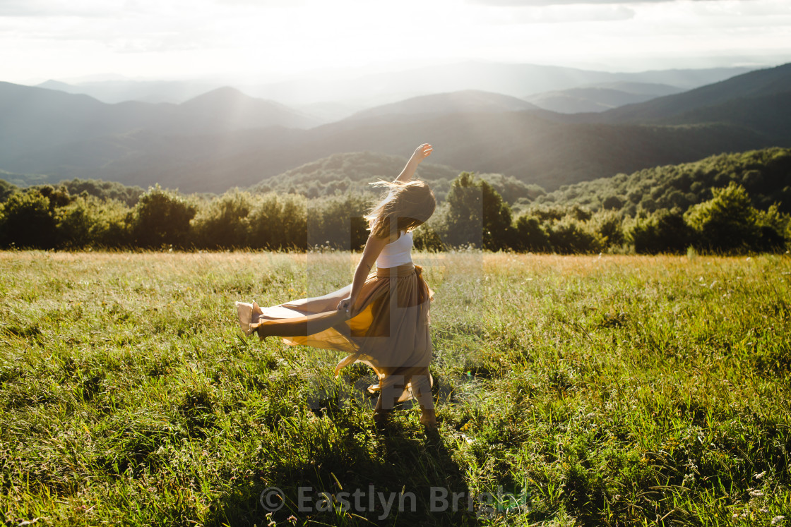 """""""Woman with long dress running in a meadow in the mountains"""" stock image"""
