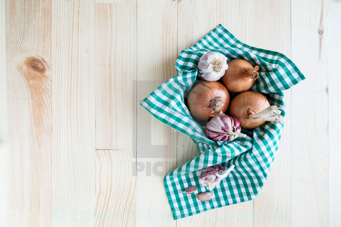 """""""composition of onions and garlic in basket on wooden table"""" stock image"""