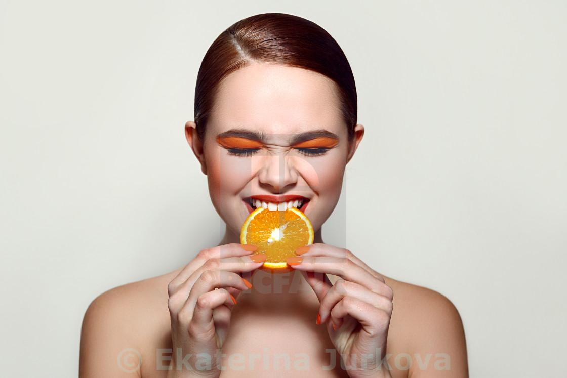 """Sour orange. The girl is tasting the fruit."" stock image"