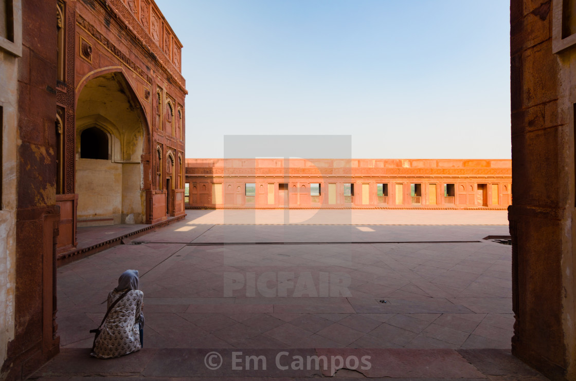"""A woman with her head covered is sitting in shade, in a courtyard of the..."" stock image"