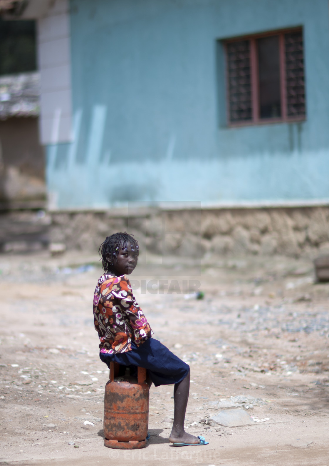 """Girl Sitting On A Bottle Of Gas, Huambo, Angola"" stock image"