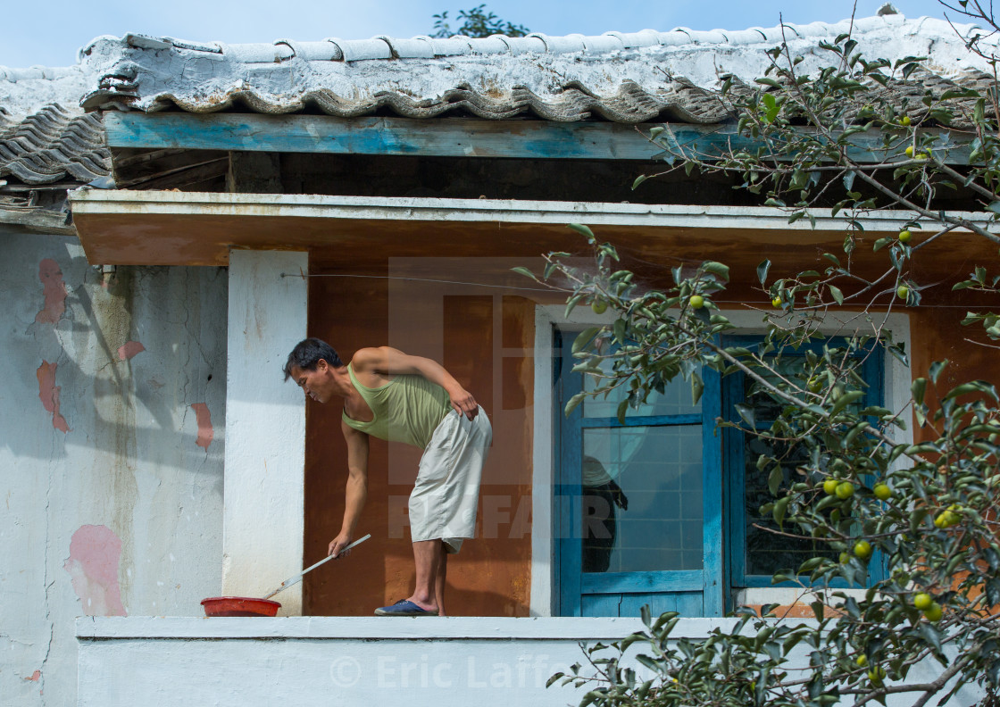 North Korean man painting his house, South Hamgyong Province