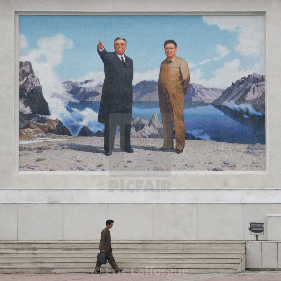 """North Korean man passing in front of a giant fresco of Kim il and Sung Kim..."" stock image"