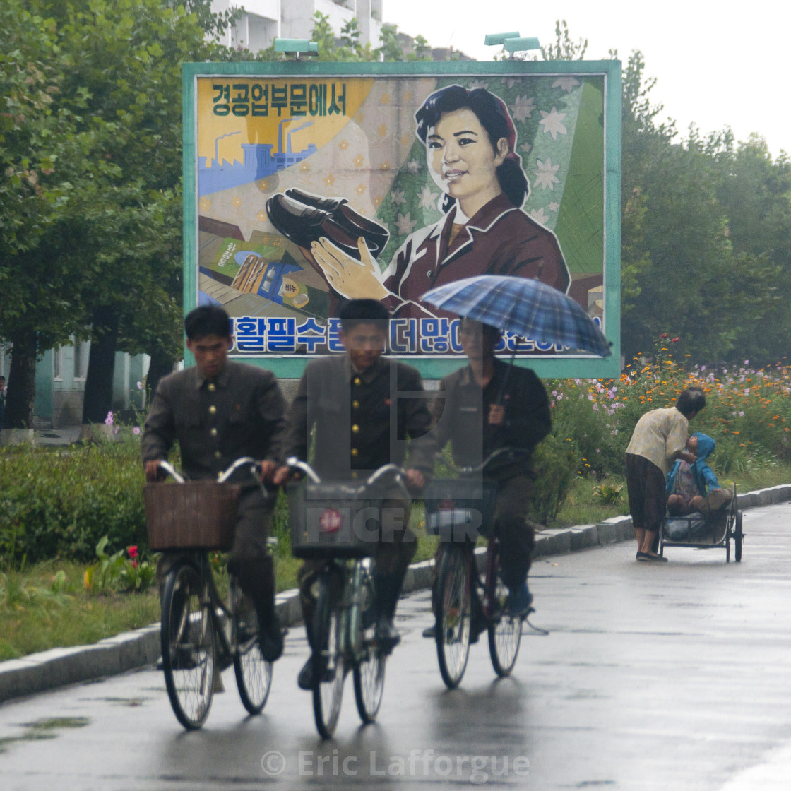 """North Korean soldiers riding bicycles on a wet road with an advertising..."" stock image"