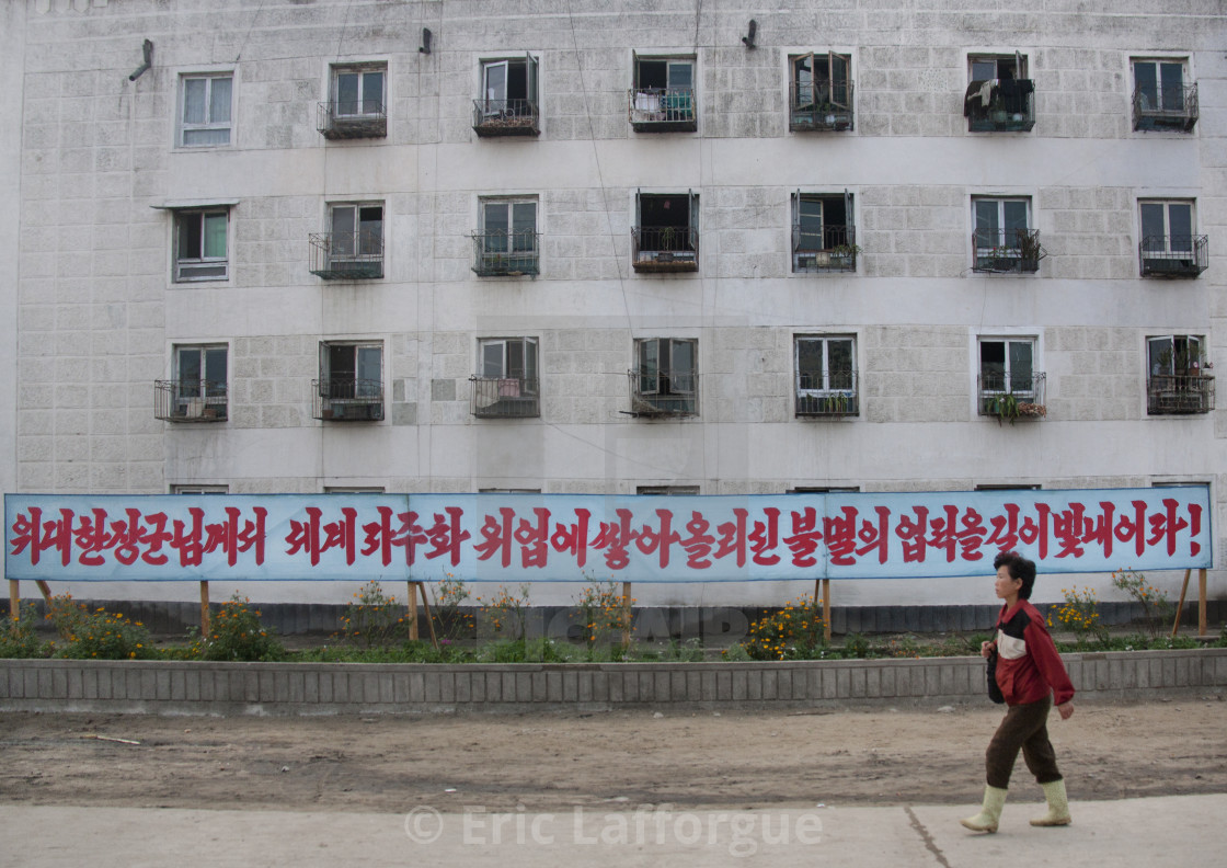 """North Korean woman walking in the street in front of a propaganda billboard,..."" stock image"