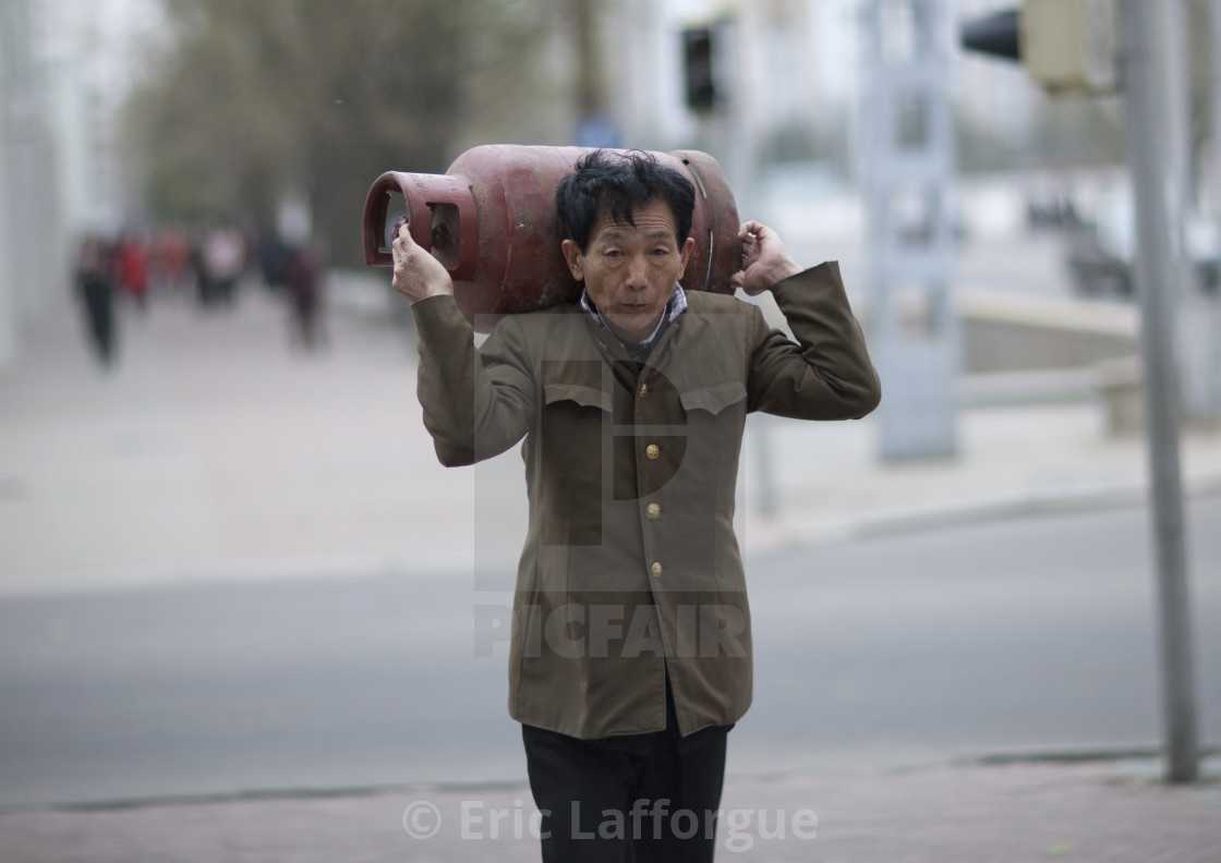 """Old North Korean man carrying a gas bottle on his shoulders in the street,..."" stock image"