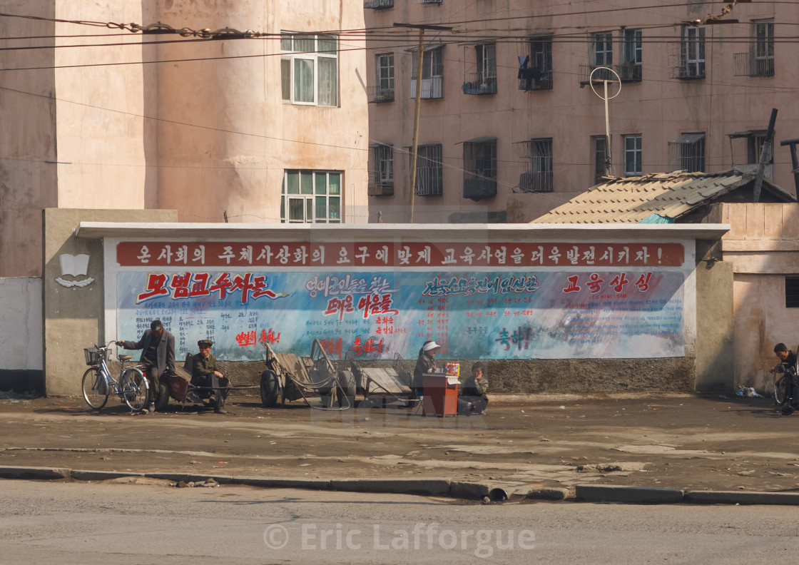 """North Korean people in the street sit in front a wide propaganda billboard,..."" stock image"