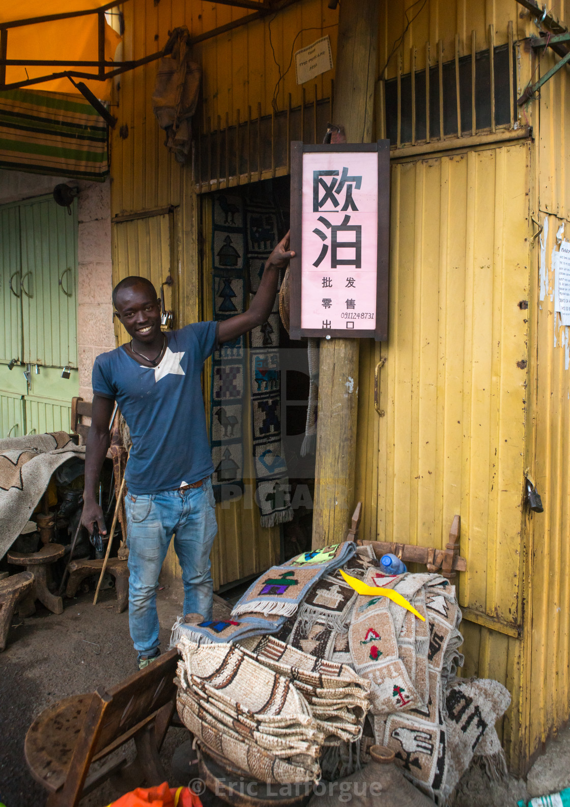 Ethiopian man in front of a billboard in chinese language to