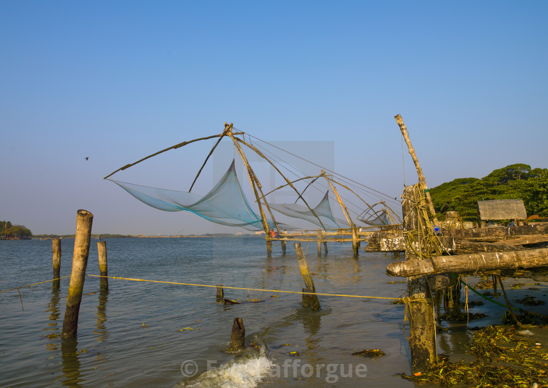 """Fishermen Sitting Near Chinese Fishing Nets, Kochi, India"" stock image"
