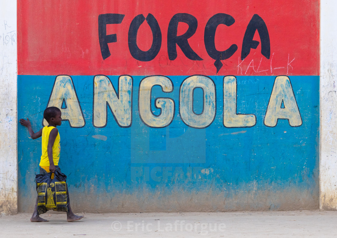 """""""Angolan boy in front of a patriotic slogan on a wall, Benguela Province,..."""" stock image"""