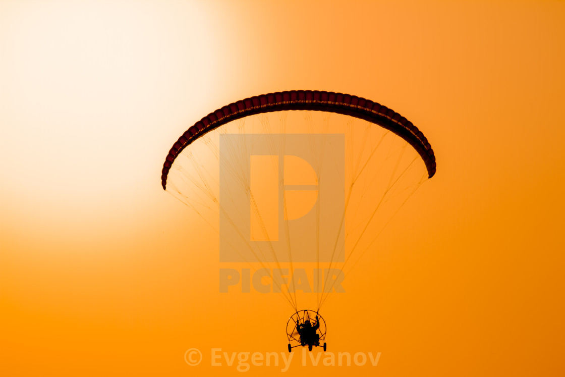 """Paraglider flying with paramotor on dramatic sunset sky with big sun in orange and yellow. Concept for adventure extreme ultra light aviation"" stock image"