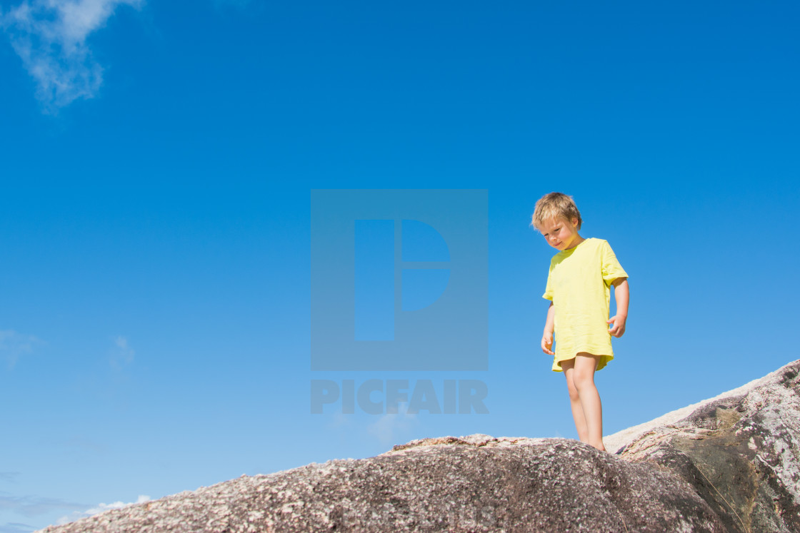 """Blond boy on a rock in front of blue sky"" stock image"