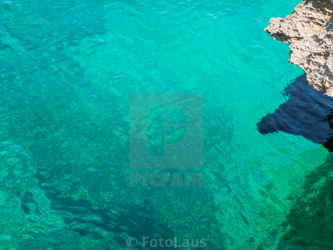 """Turquoise sea water with rock"" stock image"