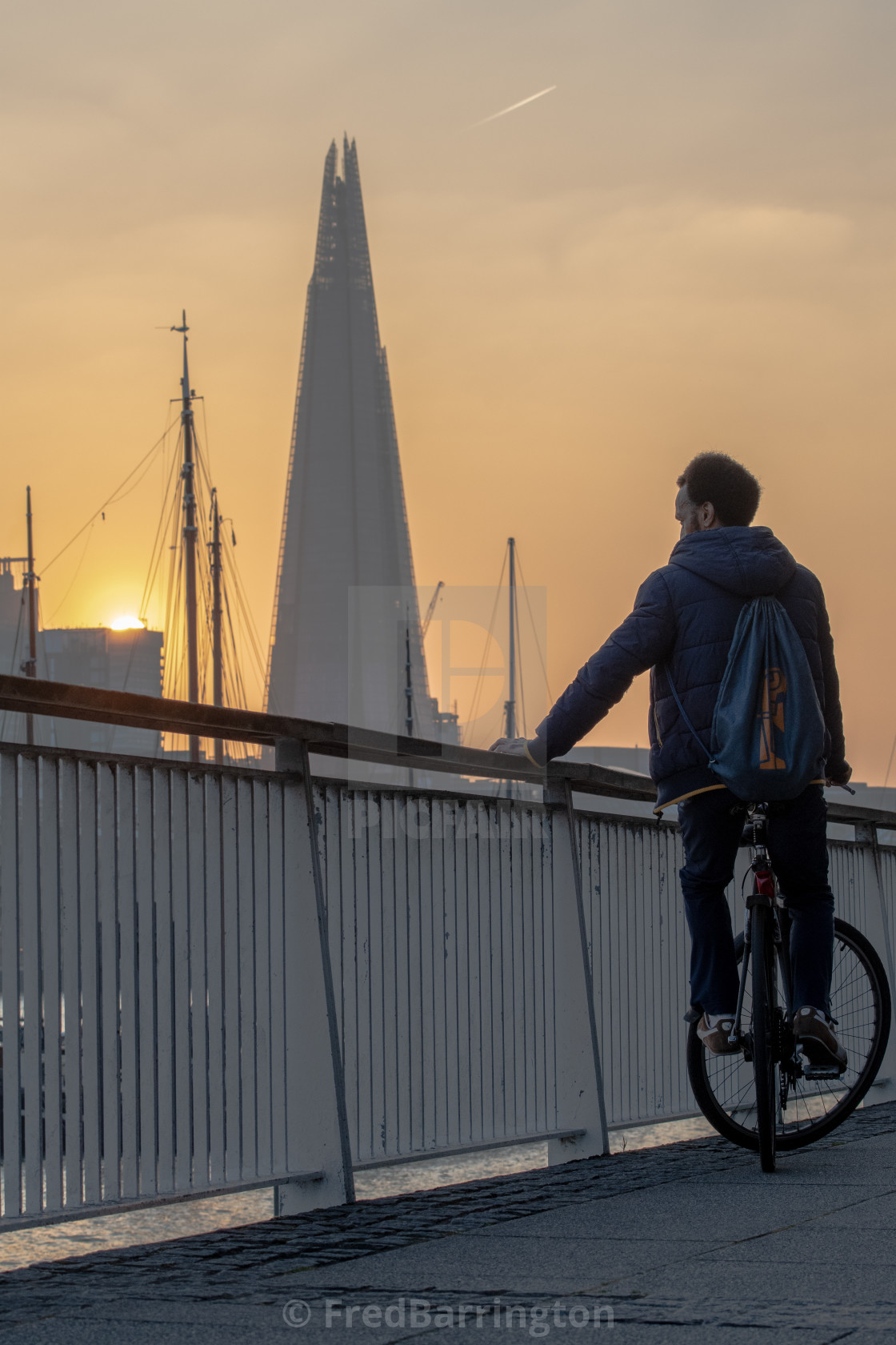 """Cyclist eyeing The Shard at sunset"" stock image"