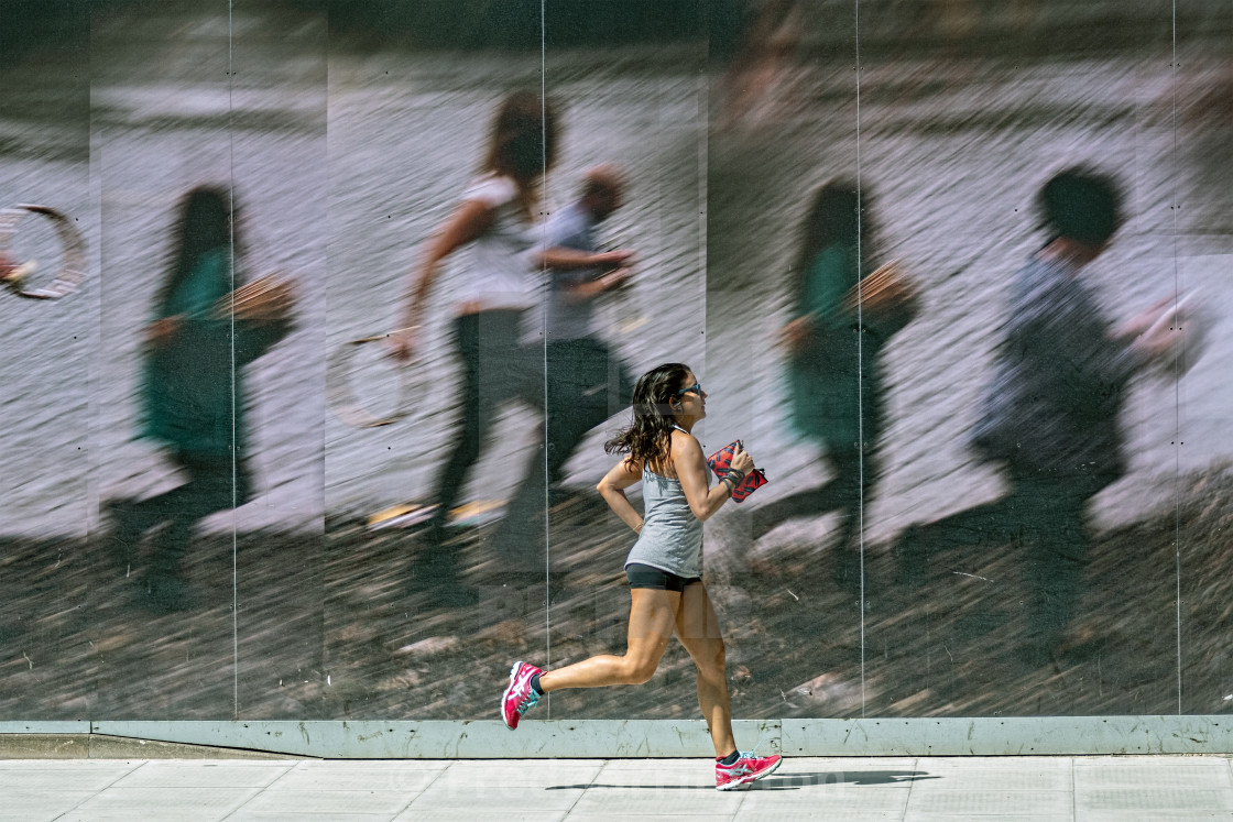 """Girl running past same billboard"" stock image"