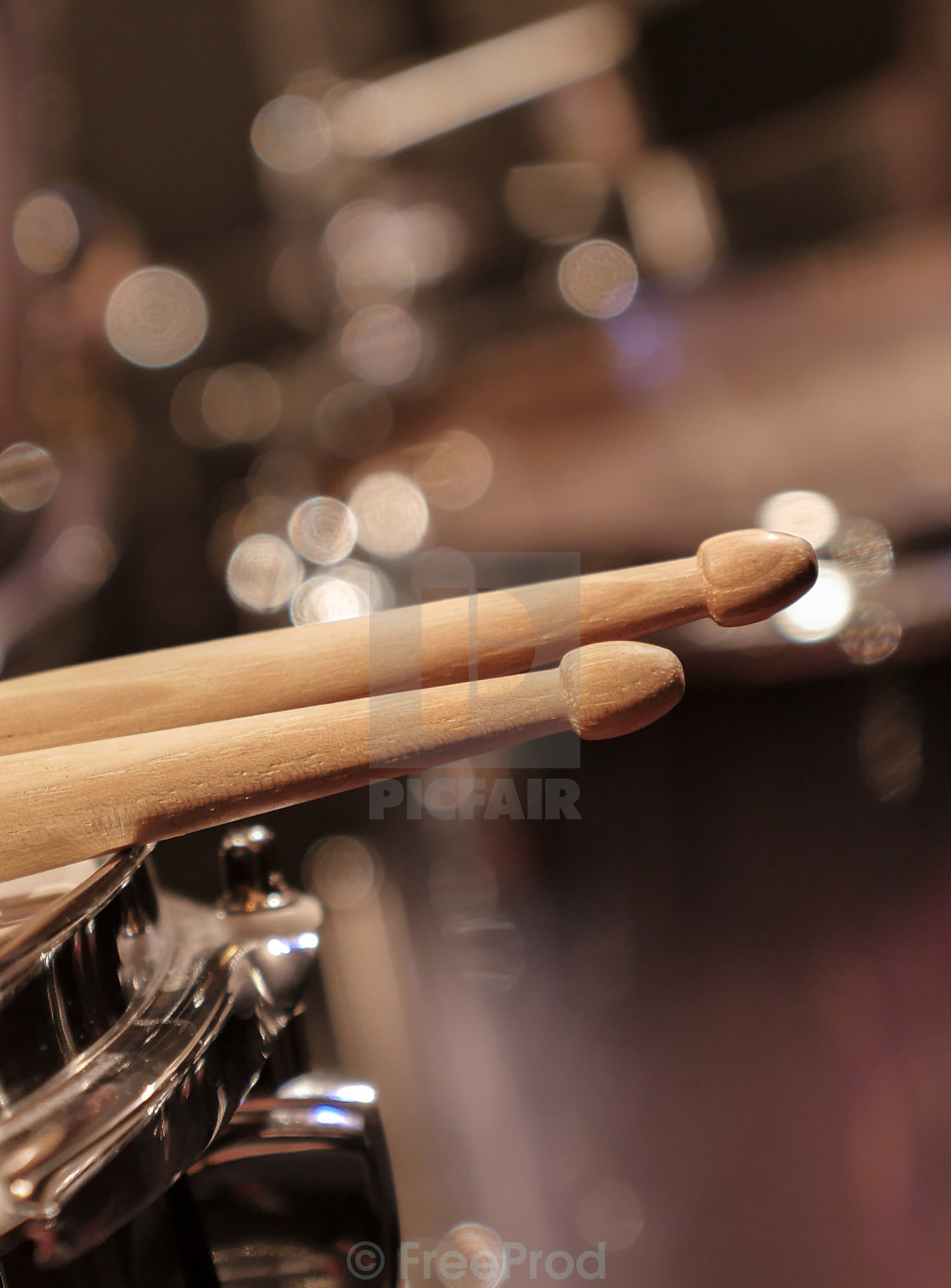 """Drum sticks lay on an drum set"" stock image"