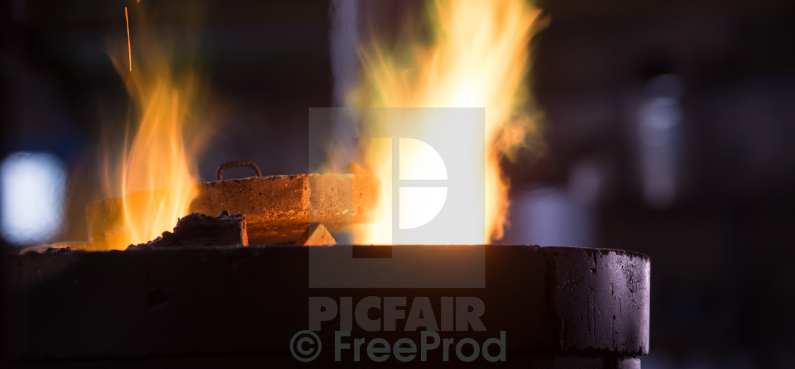 """Steel worker in protective clothing raking furnace in an industr"" stock image"