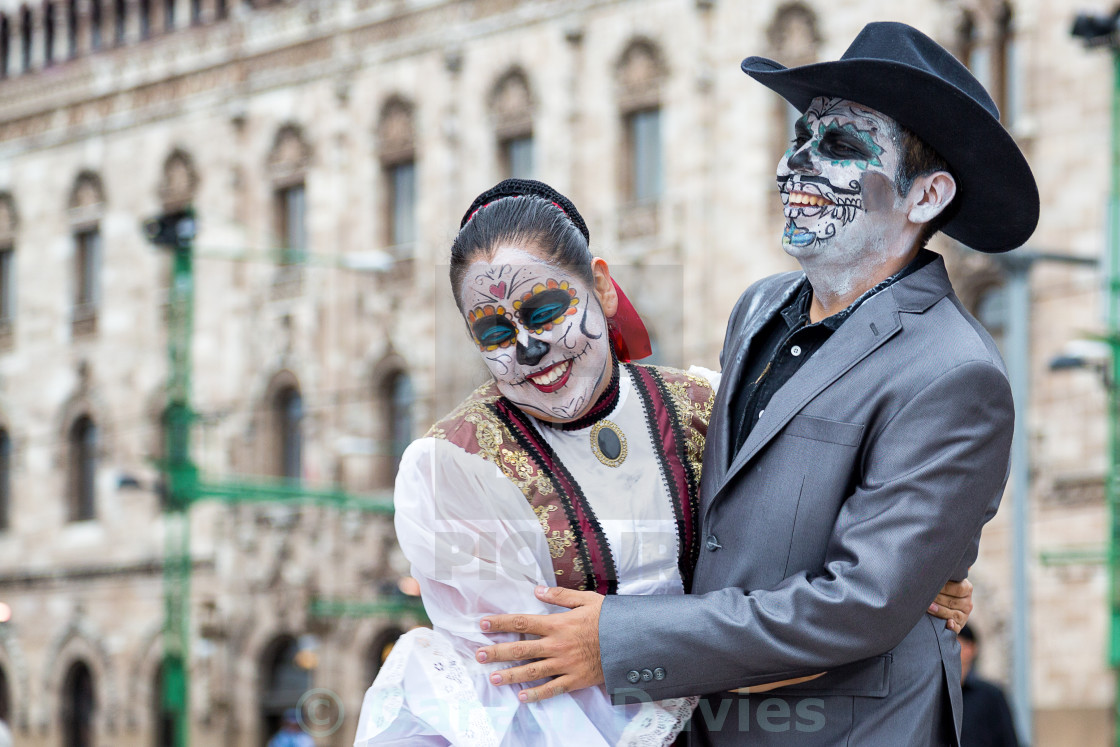 """A couple of people with their faces painted and traditional clothing for day of the dead celebrations in mexico city, mexico"" stock image"