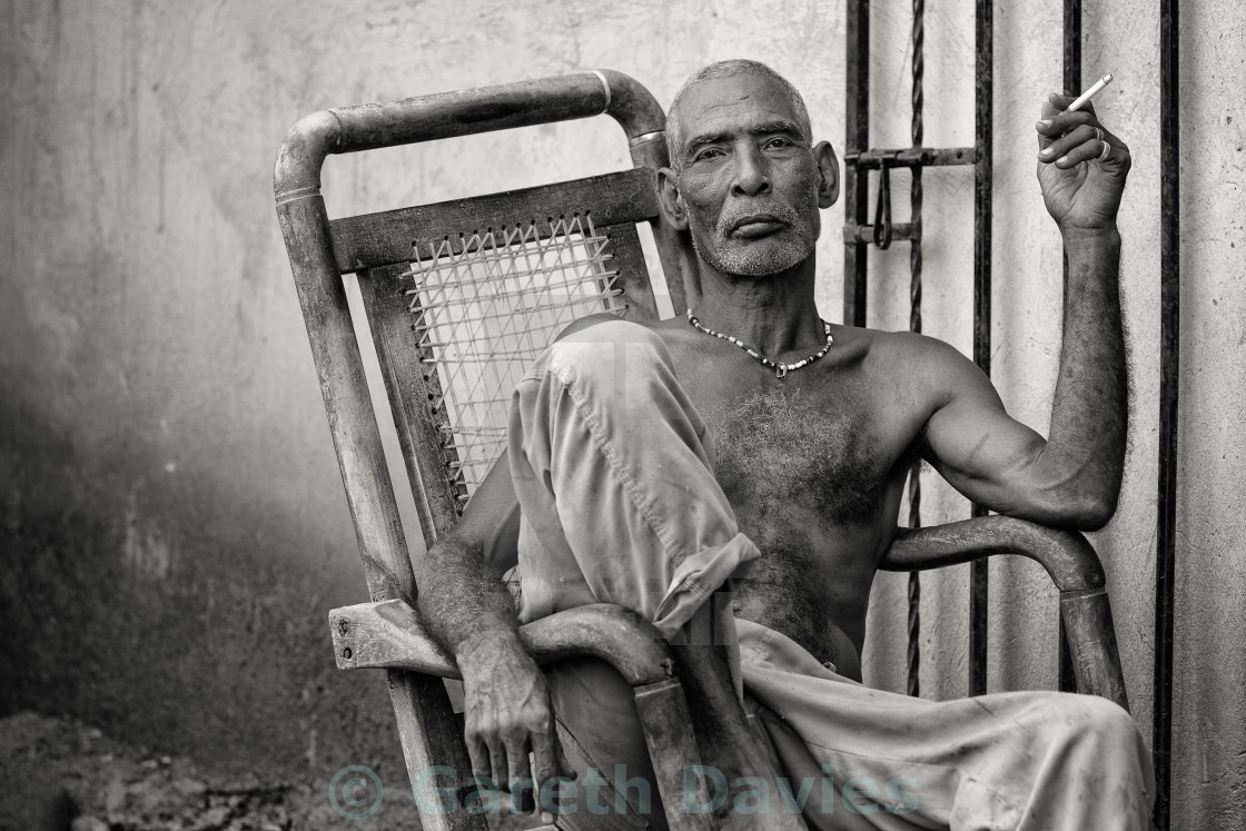 """An Afro-Latin man of slave descent, sits in a chair smoking a cigarette."" stock image"