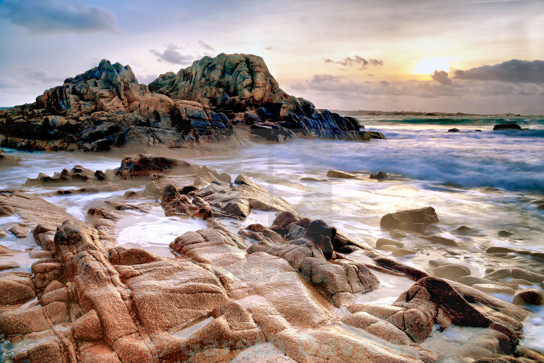 """Sunset over a rocky bay in Guernsey, Channel Islands, UK"" stock image"