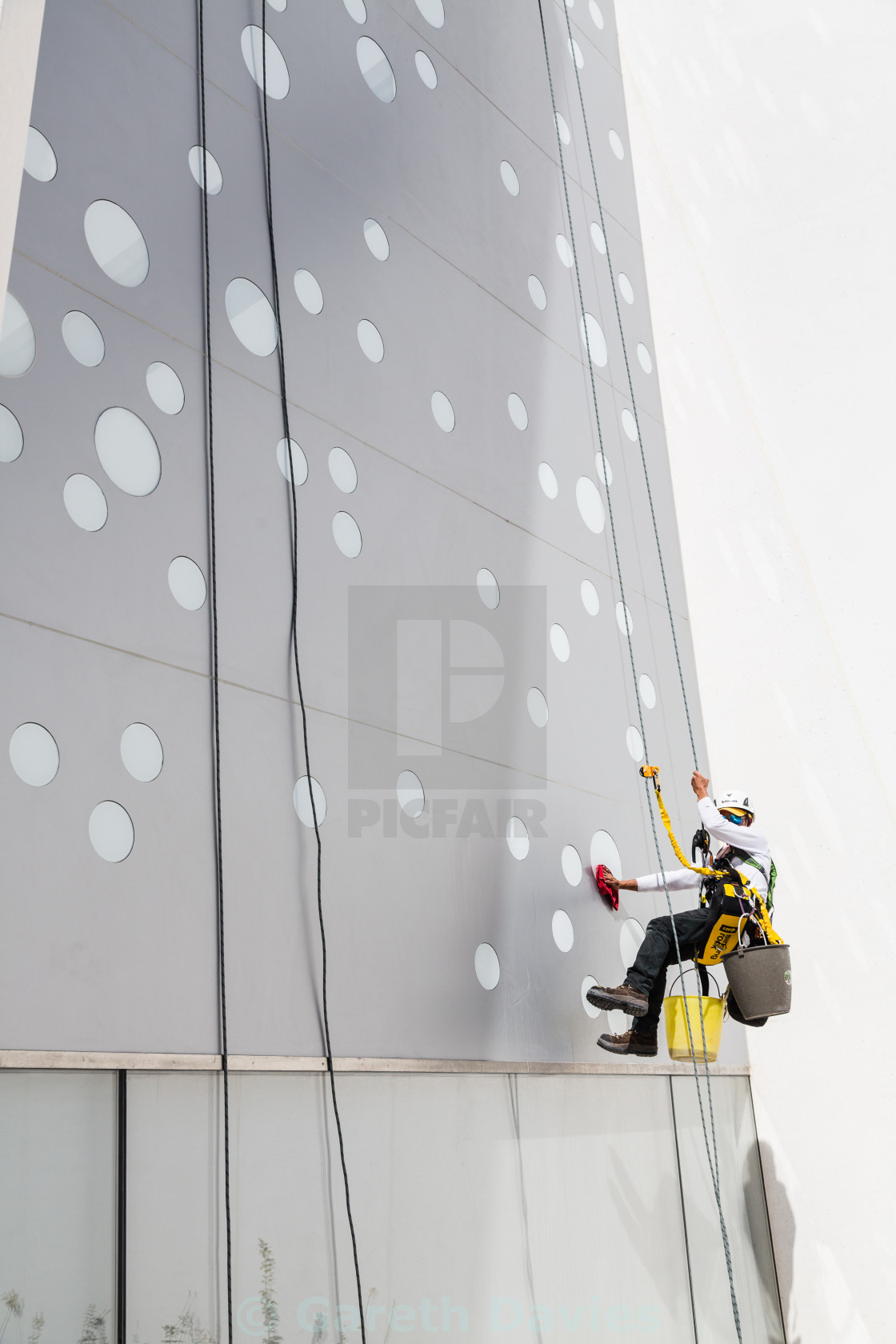 """a man cleans a window of a building suspended by a rope"" stock image"