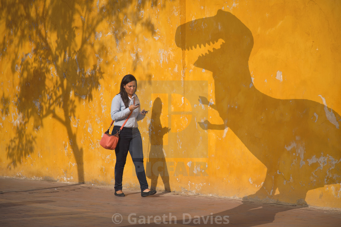 """A woman walking in the street not paying attention toon her mobile phone not paying attention"" stock image"