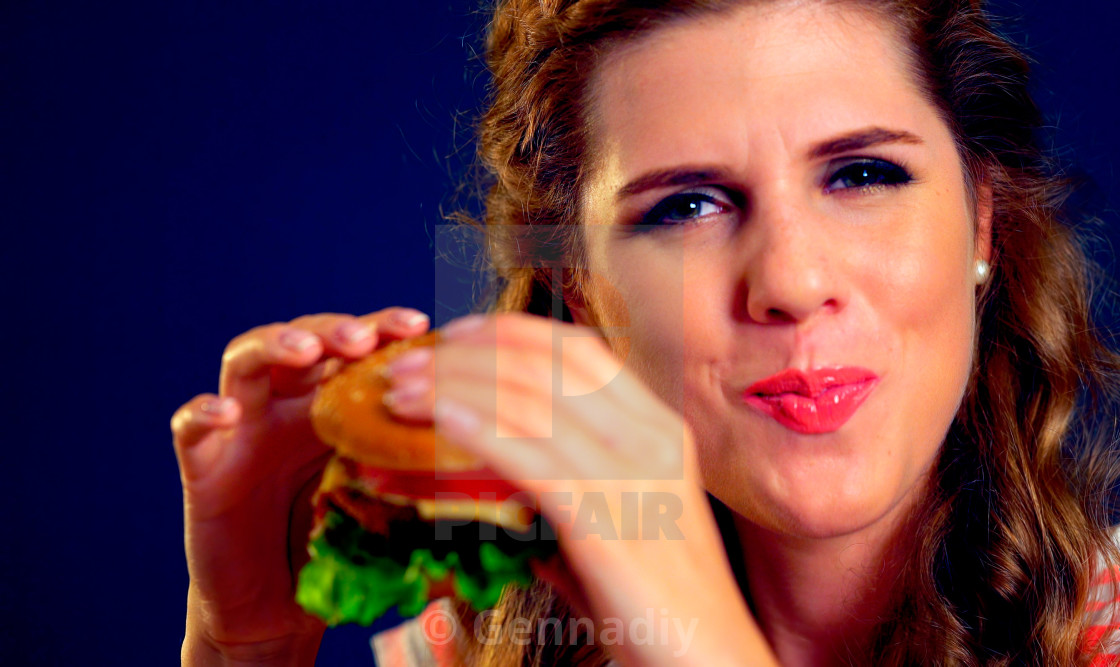 """Woman bite burger and winks. Happy student eat sandwich lunch."" stock image"
