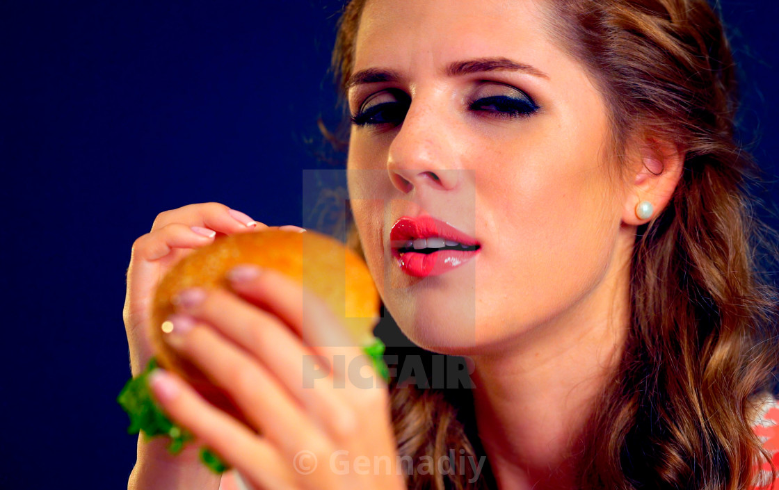 """""""Woman bite burger and winks. Happy student eat sandwich lunch."""" stock image"""