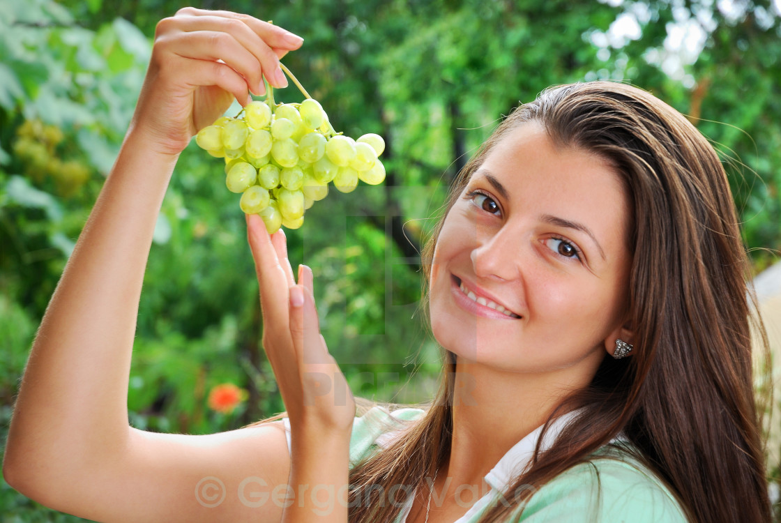 Smiling Young Woman Holding Fresh Grapes In The Garden