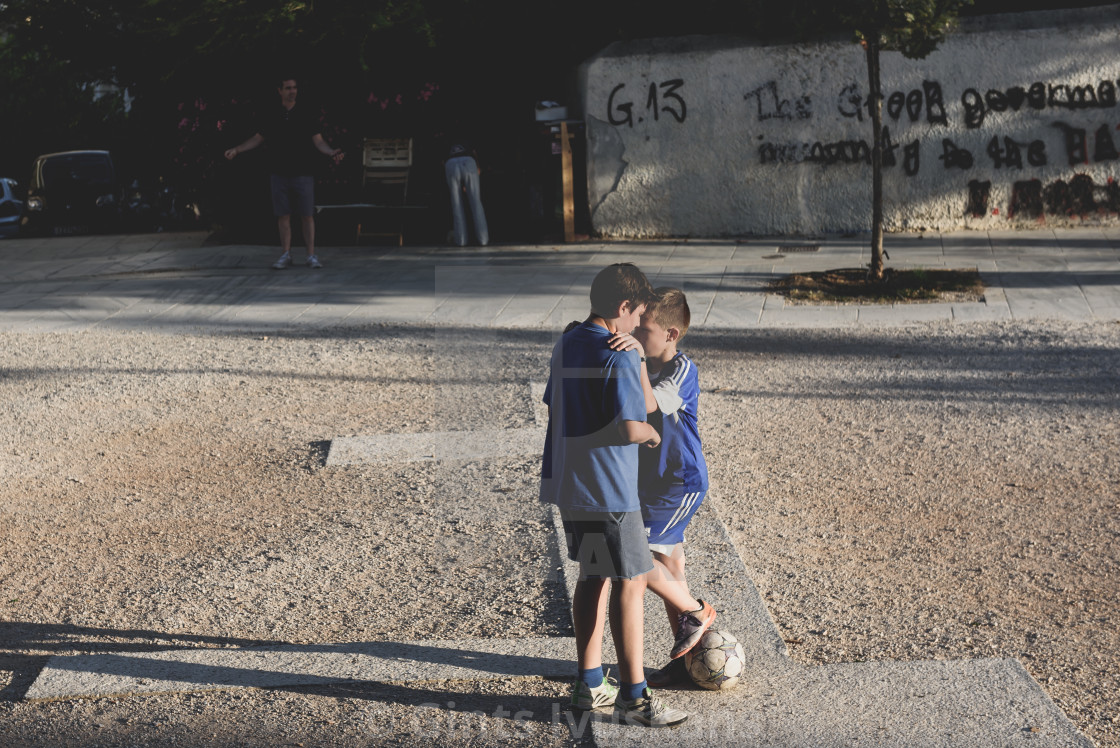 """Two boys playing football on street in Athens, Greece."" stock image"