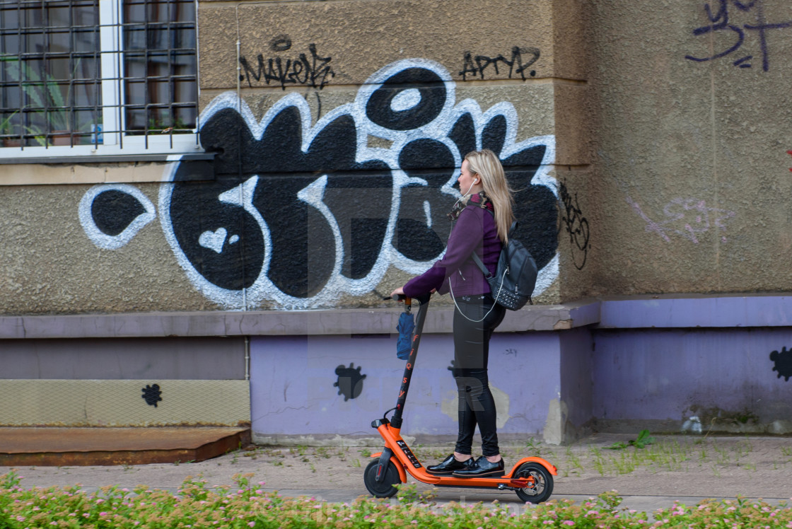 """Young woman with headphones riding with electric scooter on pavement Riga, Latvia."" stock image"
