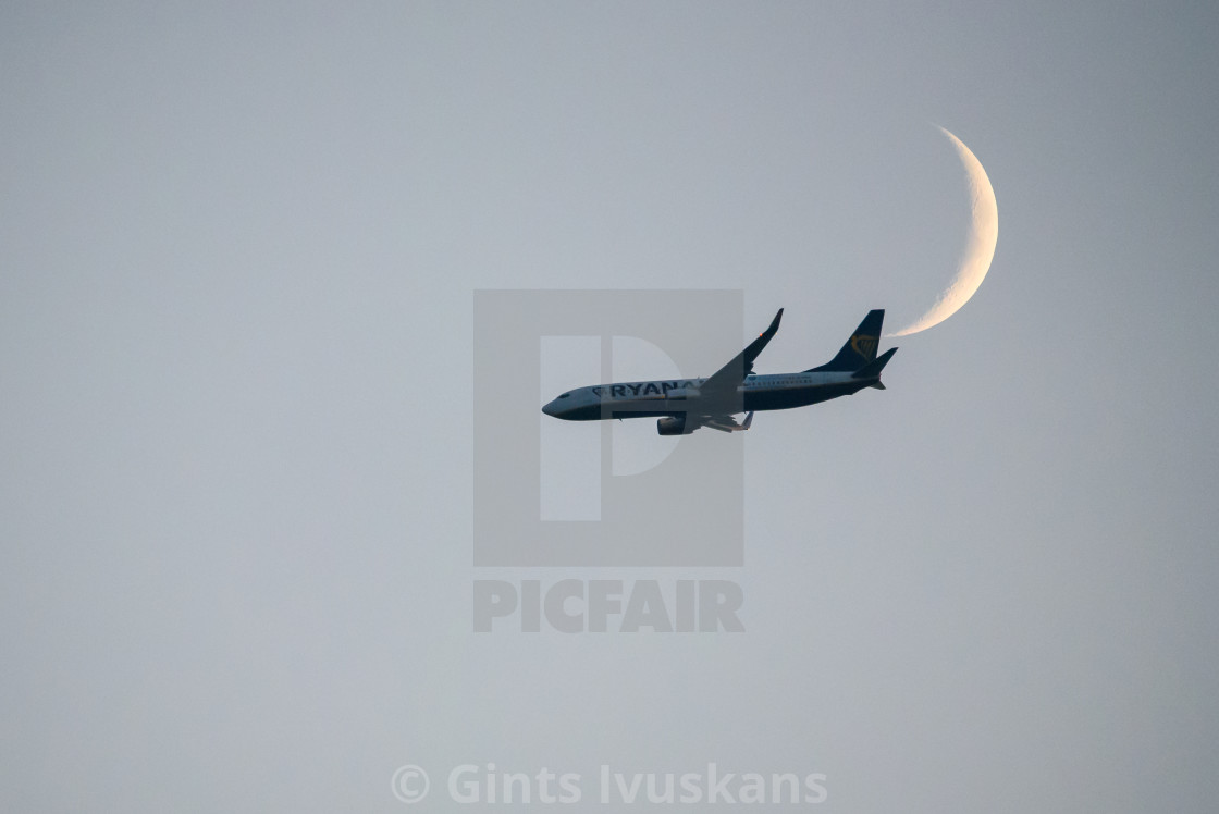 """""""Ryanair airplane flying in the sky in front of moon. Riga, Latvia."""" stock image"""