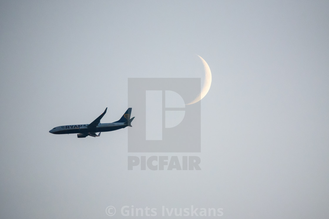 """Ryanair airplane flying in the sky in front of moon. Riga, Latvia."" stock image"