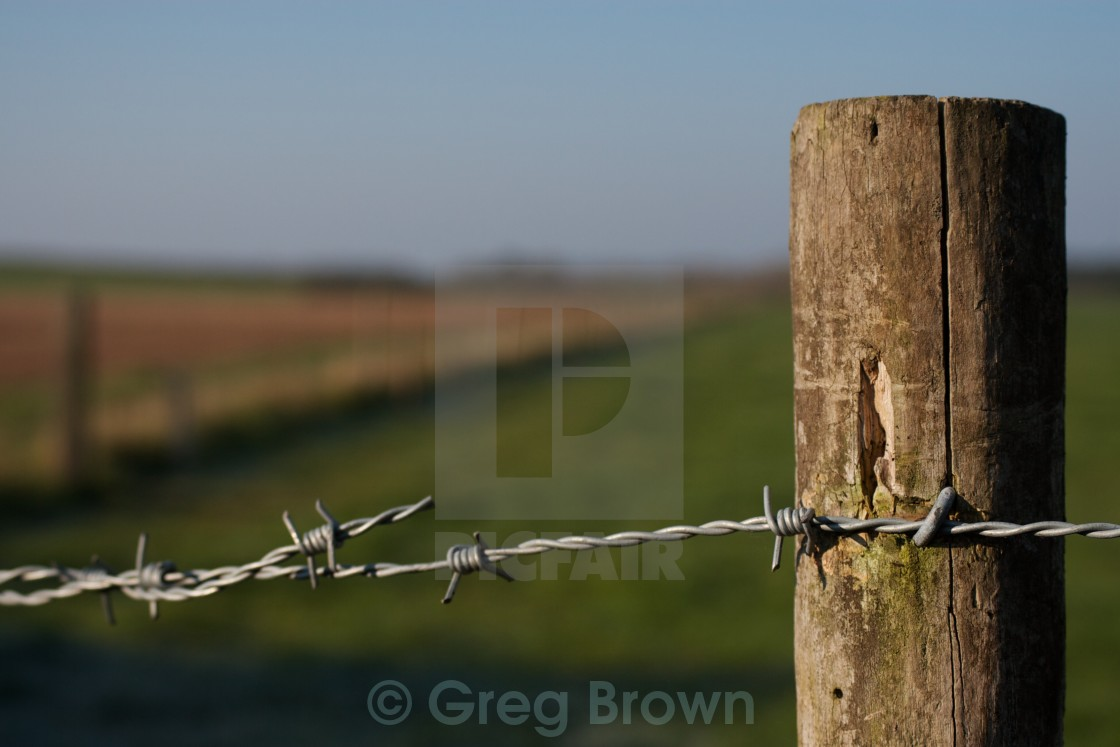"""Wooden fence post in field"" stock image"